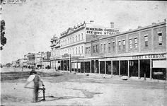 Pall mall with a man using a pump in the foreground. In the background are shops, including Henderson & Cuddisson 's Beehive Stores, Melbourne Cash Store, and Emery and Gibson. Melbourne Victoria, Victoria Australia, Old Pictures, Old Photos, Amazing Pictures, Horse Wagon, Ancient Architecture, Historical Pictures, Historic Homes
