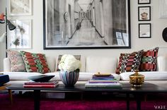 White living room with a white sofa & dominated by art