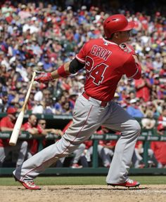 Los Angeles Angels' C.J. Cron follows through on a two-run single against the Texas Rangers, scoring teammates Kole Calhoun and Mike Trout, during the fifth inning of a baseball game, Sunday, May 1, 2016, in Arlington, Texas.