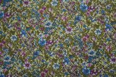 Tela para Patchwork de flores azules y malvas, predominando el fondo verde, 140 cm de ancho y 100% algodón. AGOTADA