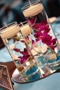 purple dendrobium orchid floating in water with floating candle. This could be done with different colors. Makes for a very pretty wedding decoration for tables or bathroom vanities and countertops.