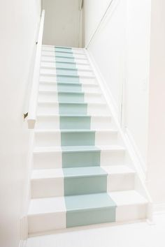 An otherwise ordinary staircase pops in a white foyer with a painted blue accent stripe.