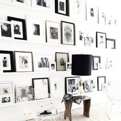 Black and white gallery wall with art leaning on shelves
