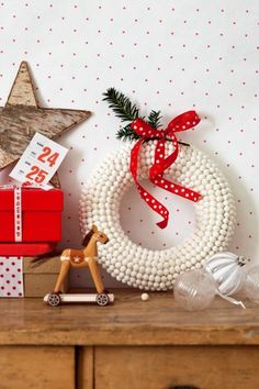 Une couronne de Noël avec des grains d'anis blancs collés sur une base en polystyrène, décorée d'un ruban rouge à pois / A Christmas wreath with beads of white anise drinks stuck on a base in polystyrene, decorated with a polka-dot red ribbon
