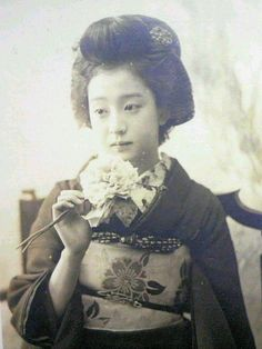 Black and white Portrait photo from early 1900s of a young Japanese Geisha Girl holding a peony blossom