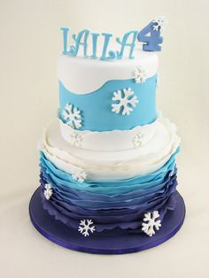 A Frozen themed cake with blue ombre vanilla layers inside. Decorated with blue ombre fondant ruffles and fondant snowflakes. Plastic Frozen figurines were added later by the customer.