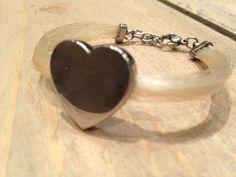 Ongevlochten armband met hart element bevestigd aan het haar. Deze kan gegraveerd worden met de naam.