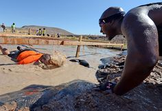 (Will Lester/Staff Photographer) A teammate yells encouragement to anther competitor as he crawls through the Electric Eel on the second day of Tough Mudder Las Vegas in Beatty, Nevada Sunday October 7, 2012.
