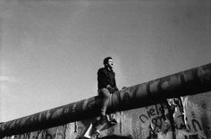 A young man bridges the wall between East and West Berlin - 1989 Click Here to Follow HISTORY IN PICS