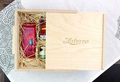 Tolótetős fadobozos ajándékcsomag faforgáccsal. A dobozban: szálas gyümölcstea, natúr kínai zöld tea /Tie Guan Yin, azaz a Kegyelem Vasistennője/, méz, úszó kannás teatojás afrikai elefántokkal. Guam, Gourmet