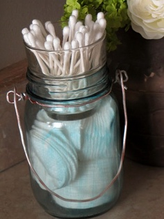 just a regular mason jar, fill it with little pads then add a votive candle holder and fill it with q-tips and voila! You have a cute and easy way to store these items in a bathroom.