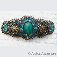 """Bead Embroidered Malachite    Bead embroidered barrette with malachite surrounded by vintage glass cabs in bronze and green blue turquoise cabs. Surrounded with high quality Japanese glass seed beads in shades of green and bronze. Accented with turquoise, swarovski crystal and copper colored glass beads. Measures 4"""" wide by 1 & 3/4"""" high, and it uses a vintage copper French clip."""