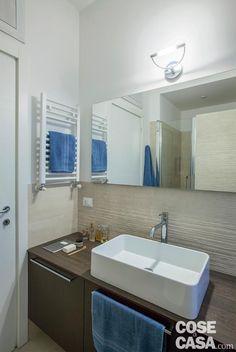 bagno, rivestimento a parete con texture in rilievo, mobile in legno tinto scuro, lavabo da appoggio in ceramica, miscelatore in acciaio cromato, specchio, applique, scaldasalviette bianco