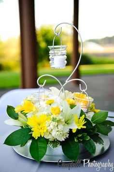 Pretty yellow and white centerpiece with flowers and candles