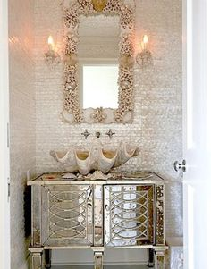 giant clam shell basin with shell sconces and yes, a reference to abalone in the wall covering..