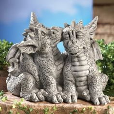 "Dragons In Love Garden Statue. This happy couple will make a unique and sweet addition to your garden or porch. Resin statue is carefully hand-painted and features two affectionate dragons, with one giving the other a smooch. Resin. 9 3/4""L x 6 1/2""W x 7 1/2""H."