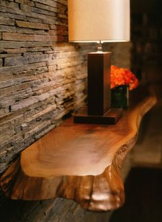 stacked stone wall with floating wood console