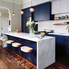 Waterfall marble countertop with wooden stools