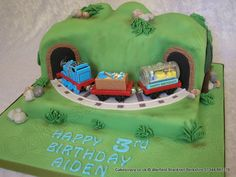 Thomas In The Valley Cake. Celebration cake carved to resemble a hillside landscape.  A sugar track bed and Thomas the Tank engine toy train in and out of the tunnel mouths.    Thomas is a real toy and belongs to Aiden, it has taken centre stage on his last three birthday cakes