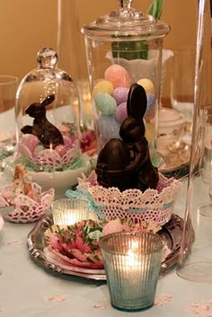 Sweet doily Easter basket with grass and eggs and a chocolate bunny under a glass cloche. Basket made with a doily and fabric stiffener over a bowl.