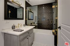 Luxury bathroom, black tile shower, gold fixtures.
