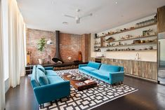 An exposed brick wall that nods to the building's industrial past spans across the length of the spacious living room. A blackened steel fireplace with a trumpeted opening contrasts against the brick walls. Spacious Living Room, Living Spaces, Manhattan Buildings, Teal Sofa, Unique Floor Plans, Brick Interior, Tile Covers, Brooklyn Apartment, Interior Decorating