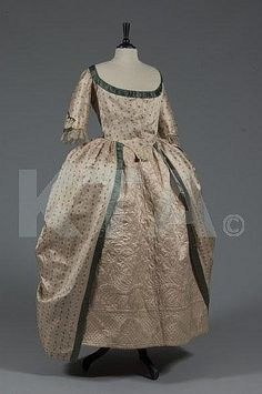 A brocaded silk open robe 'a la polonaise', circa 1785-90, of figured oyster silk woven with small floral sprigs, edged in peacock-green satin, the closed-front bodice with pointed low waist, single bone to fitted centre-back; together with a pale quilted pale pink silk petticoat adorned with quatrefoils and scrolls