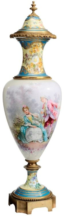 A large Sevres Style Porcelain, gilt decorated covered urn, French, 1875-1925, heavily gilt and enameled, removable cover, floral decorated neck with gilt bronze bands, body decorated with amorous couple in landscape, raised on a conforming pedestal seated on a bronze platform base