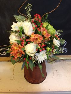 Fresh floral in moss lined small glass container. Seeded Eucalyptus, 7 white roses, 3 bunches if coral pink Hypericum Berries, 2 green Fuji Mums, 3 Orange Alstrameria, 1 white Freesia, white Waxflower & 5 white Poms. $65
