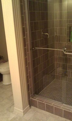 Brown tile walk-in shower and handmade wooden column
