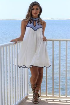 Stunning white dress with navy blue detailed crew neck. Villa Marina features an intricate neck design with cutouts and button closure. Material is Cotton Bust
