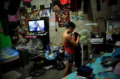 """Diana Olmos, 14, folds laundry at her home on the 7th floor of """"Tower of David."""" Squatters live in the bottom 28 floors of the 45-story uncompleted skyscraper, located in downtown Caracas, Venezuela. More than 2,500 squatters now occupy the building."""