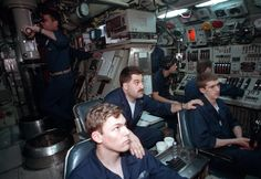 A chief petty officer talks to the helmsmen aboard the nuclear-powered attack submarine USS PARGO (SSN-650) (Sturgeon Class) as CDR David W. Hearding, the submarine's commanding officer, looks through the periscope. The PARGO is underway north of the Arctic Circle.