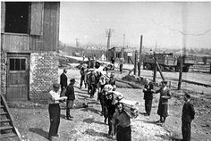 Jewish prisoners carry bolts of cloth to the Madritch factory in Plaszow. The Madritch factory utilized concentration camp labor to produce uniforms for the German army.  Photo credit: Leopold Page Photographic Collection,