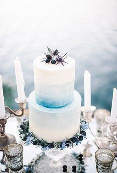 A small accent of berries tops this two-tiered wedding cake that features a color wash of cool blue.