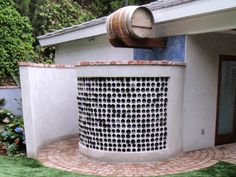 "The circular ""tiles"" in this round, custom shower enclosure come from old wine bottles. Designer Scott Cohen used them to create a focal wall that lets in light but maintains privacy. An old wine bottle serves as the water spout."