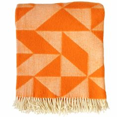 Tina Ratzer Twist A Twill Orange Blanket: The design is a modern take on a traditional patchwork quilt. The triangle is twisted and turned across the surface of the throw to emphasise the three-dimensional shadow effect that appears when using it.