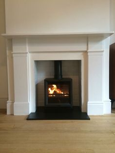 Stovax wood burning stove with slate hearth and white tiled opening.