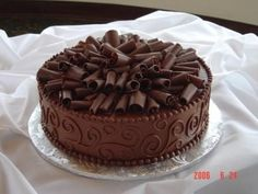 Chocolate fudge cake w/ choc buttercream and chocolate curls.  The mounded up chocolate curls would be a great way to top a chocolate cake