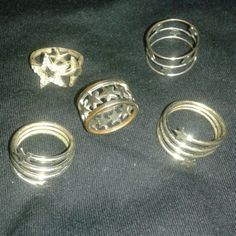 FIVE silver star design rings (used/tarnished) Bundle of five silver rings in various star designs. Two are spiral thumb rings. THESE ARE USED so they have signs of wear and some tarnish. I *THINK* they are a size 5 or 6 but I could be wrong!! Originally purchased at Claire's stores. Claire's Jewelry Rings