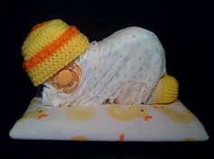 diapers creatively shaped into baby with the help of receiving blankets a soother and knit cap and booties