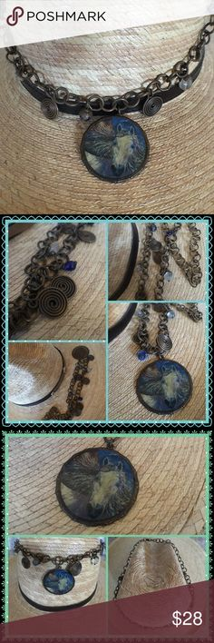 """Horsin Around Unique necklace with antiqued bronzed style detail.  Created with simple blue beads and matching rolled circles.  The magnificent image of a white stallion horse is a smaller version of a hand painted piece of art. Unique stylish piece.  Rugged and earthy a piece to treasure. The chain hangs down 9 3/4"""" with the horse medallion 1 1/2 circumference. Worn for a rodeo event. Jewelry Necklaces"""