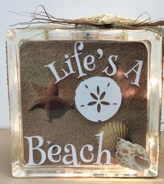 """Lighted Glass Block sample I made for A.C.MOORE.  """"Life's a Beach"""" vinyl cling.  Used beach memory paper inside and dimensional shell sticker on front.  Burlap ribbon, and a real star fish glued to top finish the look."""