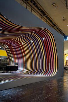 Stand en la feria de revestimiento de suelos Domotex. La estructura lineal de colores cubre todo el espacio haciendo una continuidad entre suelo, paredes y techo e invadiendo de textura todo el volumen.  #Esmadeco.