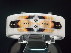 The Phoenix American Indian Beaded Bracelet with a Frosted Crystal Background. The Phoenix Design is created using soft red, orange and yellow with flat tan and black feathers. The base used for this bracelet is copper wrapped in a soft white deerskin. Glass seed beads are then sewn with patients and care onto the deerskin in this Phoenix pattern . The colors pop out of this Southwestern bracelet. This bracelet measures approximately 1 inch wide and will fit wrists size of 6, 7 and 8 inches. The copper band used for the base for this bracelet is adjustable by simply bending the bracelet around your wrist. I enjoyed creating the bead work on this piece of finely detailed Native American jewelry. This bracelet is signed and comes with a certificate of Authenticity. Thank you for looking at my Cherokee beaded jewelry.