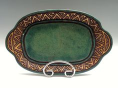 This platter was handmade from a compressed slab of speckle brown clay. After forming it was hand carved with a unique Aztec type design all the