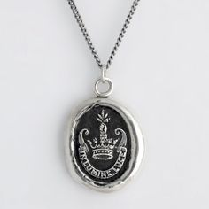 Inspiration Talisman Necklace - This handcrafted talisman necklace reads In Lumine Luce in Latin, which means Shine In The Light. The arm coming out of a crown is symbolic of leadership and achievement. It is holding a sheaf of wheat which represents achieving one's hopes and dreams.
