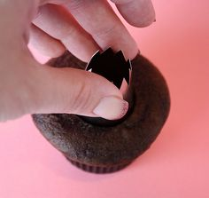 Using the bottom of an icing tip to cut a hole in cupcakes for filling.  Good to know :)