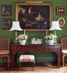 Herringbone floors, antique sideboard with carved Greek key trim, oil paintings, silver, symmetrical styling, mossy green walls