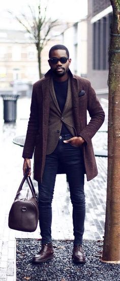 Fall fashion inspiration with a brown topcoat navy polka dot pocket square skinny denim jeans brown wool blazer black t-shirt sunglasses brown leather duffle bag brown leather shoes. model unknown. #fallfashion #falloutfits #menswear #menstyle #mensapparel #topcoat #dufflebag #blazer #mensfashion